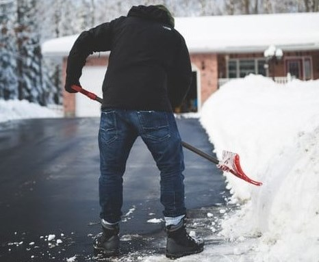 man shoveling snow to clear his driveway