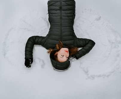 a women lays in the snow making a snow angel by fanning out her arms and legs to make wings in the snow