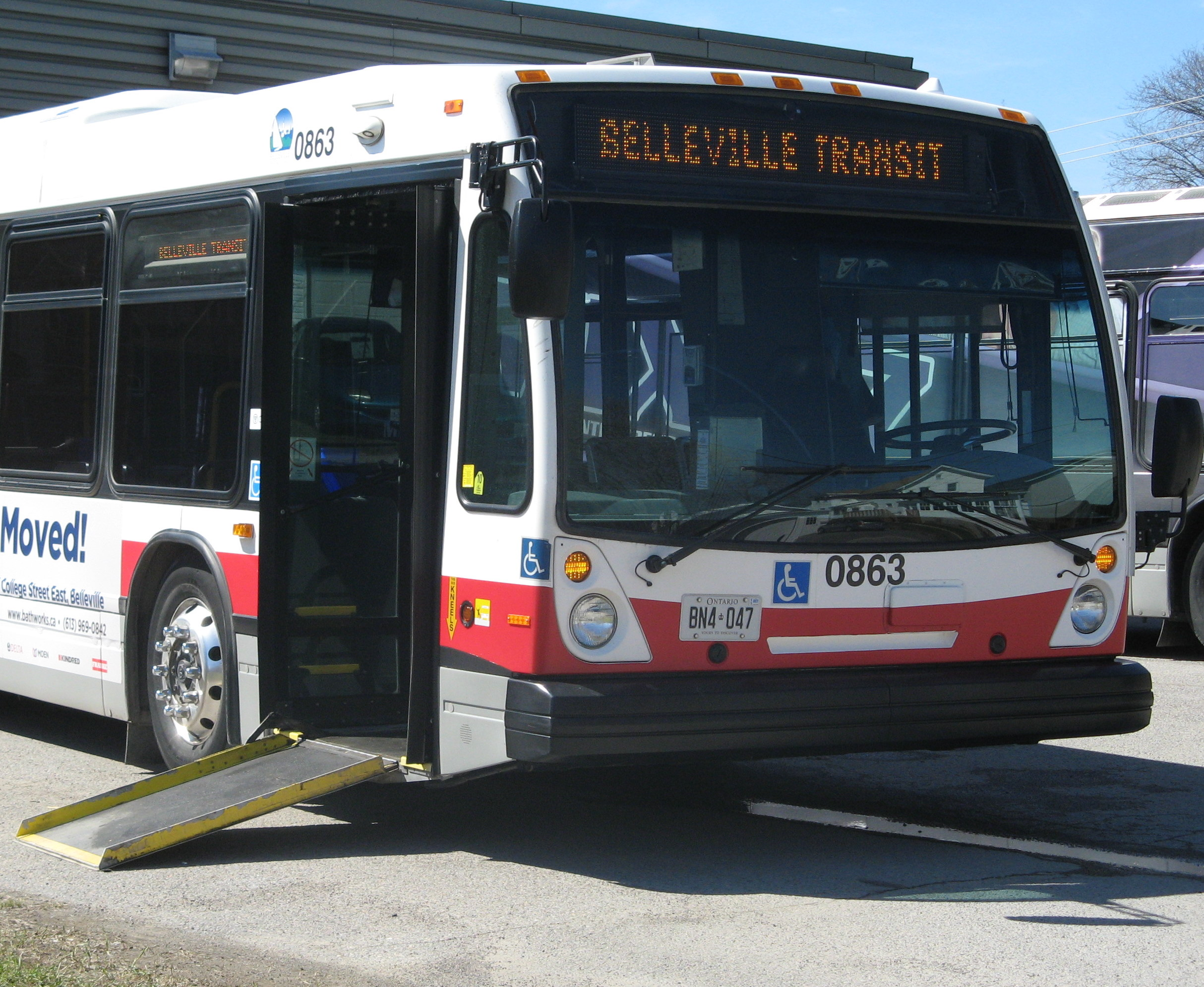 a conventional transit bus from Belleville Transit lowers the front entrance and deploys the ramp for easier boarding