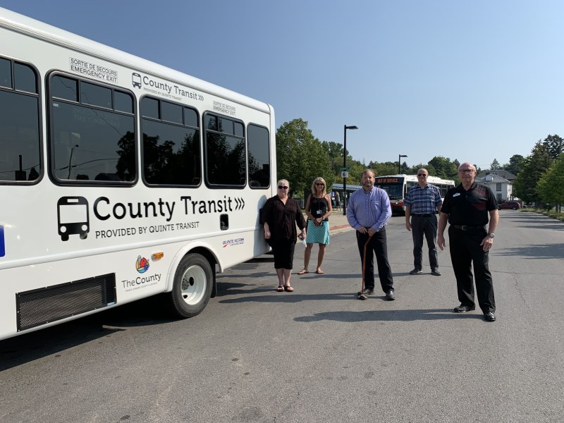 Quinte Access Executive Director Shelly Ackres, Prince Edward County Community Services and Programs Coordinator Grace Nyman, Transit Manager Paul Buck, Prince Edward County Director of Community Services, Programs and Intiatives Todd Davis and Councillor Bill Sandison stand beside the first County-Belleville bus at the Belleville Transit Terminal.
